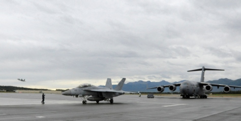 An F-18 Hornet returns from a mission, an F-22 Raptor takes to the skies, and a C-17 Globemaster prepares for a mission during Red Flag-Alaska 14-3 Aug. 8. Red Flag- Alaska is a joint/coalition exercise designed to help militaries from all over the world hone their skills in simulated combat. (U.S. Air Force photo/Staff Sgt. Wes Wright)